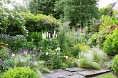 Flowering perennials and feather grass next to stone-flagged path in summery garden
