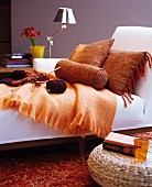 Orange cushions and knitting on white chaise longue