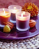 Lit scented candles on purple plate decorated with physalis husks