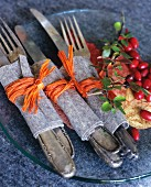 Cutlery wrapped in felt and raffia on glass plate