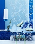 Folding sofa in front of blue wall seen through delicate screen
