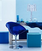 Blue plastic chair and cubic pouffe around glasses and lamp on table