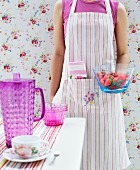 Woman wearing striped apron standing in front of floral wallpaper holding bowl of strawberries