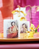Candle decorated with picture of Oriental woman playing a pipa next to orchid flower