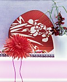 Artificial flower in front of red Oriental fan and orchid