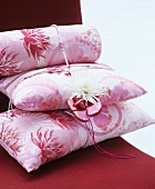 Stack of pink floral cushions decorated with dahlia and baby shoes