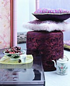 Floral cushions on pouffe behind bowl of cherries