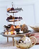 Silberglänzende Etagere mit Obst, Kunstblumen und Kerzen dekoriert, davor goldglänzende Teekanne
