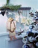 Wooden Christmas angel and letters spelling XMAS hung from rustic coat rack next to Christmas tree decorated in pastel blue