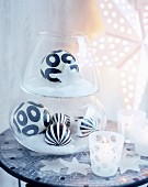 Black and white patterned baubles in glass vessels on mosaic-tiled table