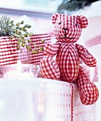 Red and white gingham teddy bear arranged on top of presents