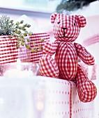 Teddybär aus rot-weiss kariertem Stoff auf Geschenken arrangiert