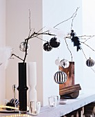 Elegant baubles and bird ornaments on bare branch in black vase