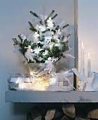 Green fir branches decorated with white feathers and angel ornaments in glass vase