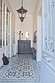 Hall in shades of grey with patterned tiles, lanterns and stucco ceiling