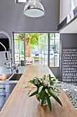 Modern stainless steel kitchen with industrial lamps and windows