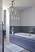 Elegant bathroom in shades of grey with panelled bathtub and chandelier