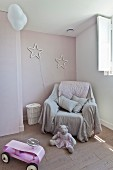 Throw on armchair below stars on wall in child's bedroom