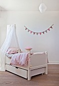 Free-standing bed below canopy in front of bunting on wall