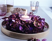 Lit, white floating candle in wreath of purple pot pourri