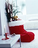 Red foot warmer used as Christmas stocking filled with gifts and branches