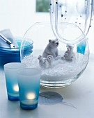 Polar bear figurines and artificial snow in glass vase next to tealights in blue glasses
