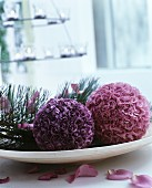 Two balls of fabric flowers and pine sprigs on dish