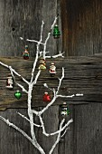 Christmas decorations hung on white-painted branch against rustic wooden wall