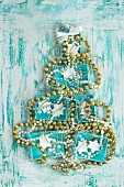 Turquoise boxes and strings of beads arranged in the shape of a Christmas tree