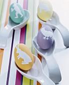 Gefärbte Ostereier mit verschiedenen Motiven auf Porzellanlöffeln arrangiert