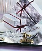 Mit Spitzenbändern verpackte Geschenke auf einem Spiegeltablett