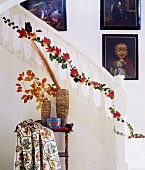 Strand of ivy and red autumn leaves twining up staircase balusters