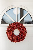 Wreath of red berries below fanlight in front door