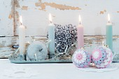 Pastel candles on tray and Christmas-tree baubles with crocheted covers
