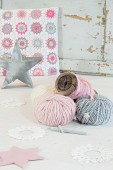 Balls of pastel wool in front of crocheted cushion cover