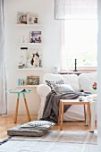 Comfortable white sofa with loose cover, scatter cushions and blanket next to books on floating shelves; Scandinavian ambiance