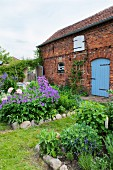 Brick house surrounded by cottage garden with stone-edged flowerbeds