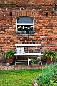 weiße Bank vor einer Backsteinfassade im Garten