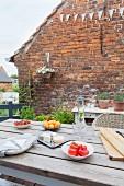 Gedeckter Tisch auf der Terrasse vor einer Backsteinwand