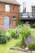 Flowerbeds edged with stones in cottage garden outside barn