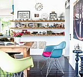 Colourful designer chairs and floating shelves in eclectic dining room