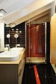 Floor-level shower under sloping roof in bathroom
