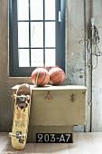 Skateboard and basketballs on old trunk below industrial window