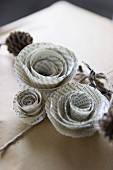 Roses made from pages of old book decorating gift-wrapped present