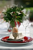 Place setting with Easter breakfast egg on table in garden