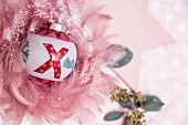 Painted Christmas bauble surrounded by delicate pink feathers