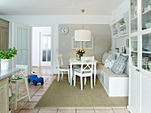 A white living room-cum-kitchen with a comfortable bench, a cabinet and a tiled floor