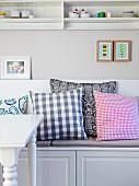 weiße Sitzbank mit verschiedenen Kissen unter Wandregal im Landhausstil