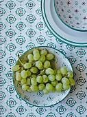 Weintrauben in Schale mit grün-rotem Muster auf gleich gemusterter Tischdecke