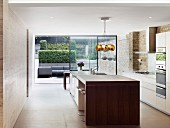 Modern designer kitchen with glass wall and view of terrace in modernised period building